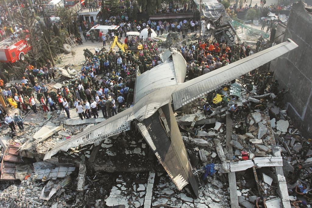 Rescuers search for victims at the site where an air force cargo plane crashed in Medan, North Sumatra, Indonesia, Tuesday. (AP Photo/Yudha Lesmana)