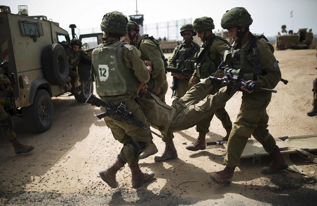 IDF soldiers carrying their comrade during a military exercise in the region bordering the Gaza Strip on Sunday. (REUTERS/Amir Cohen)