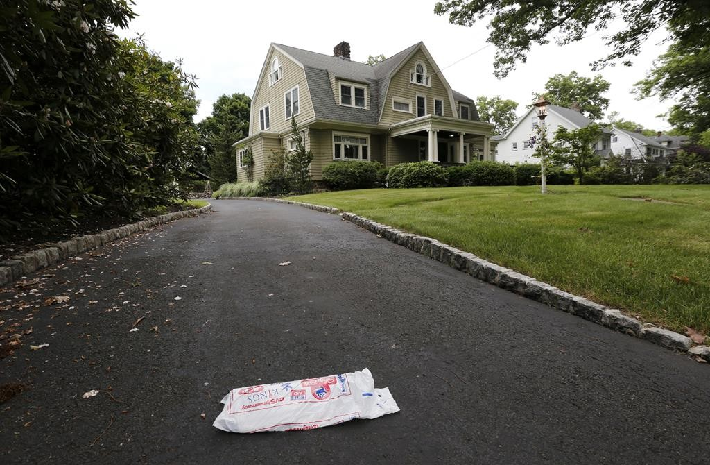 A newspaper rests unpicked Thursday on the driveway of a home in Westfield, N.J. which has been receiving creepy letters from a stalker. (AP Photo/Julio Cortez)