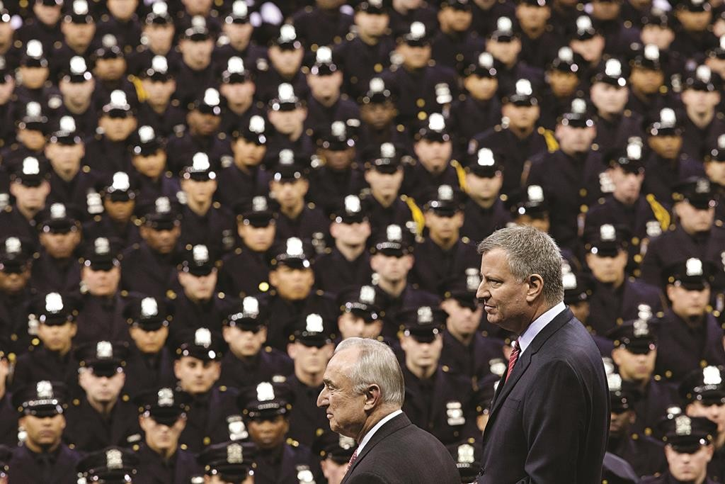 Mayor Bill de Blasio (R) and NYPD commissioner Bill Bratton stand on stage during a New York Police Academy graduation ceremony last year. (AP Photo/John Minchillo)