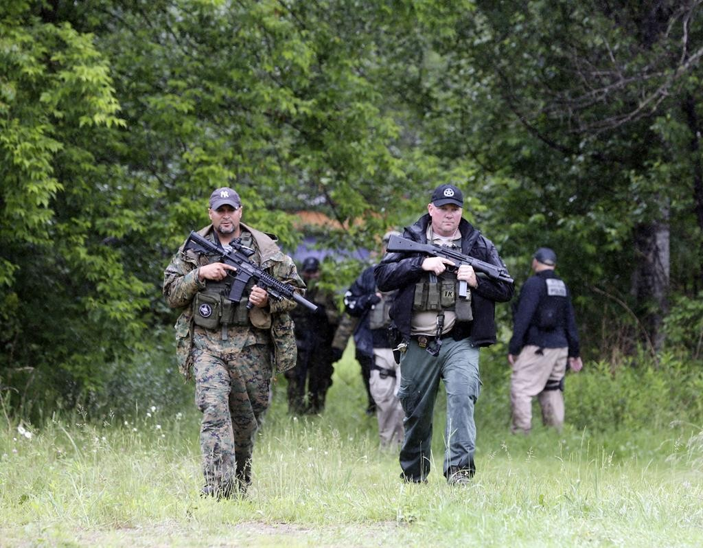 AP Photo/Mike Groll Law enforcement officers on Monday during the 10th day of the manhunt for the two prison escapees.