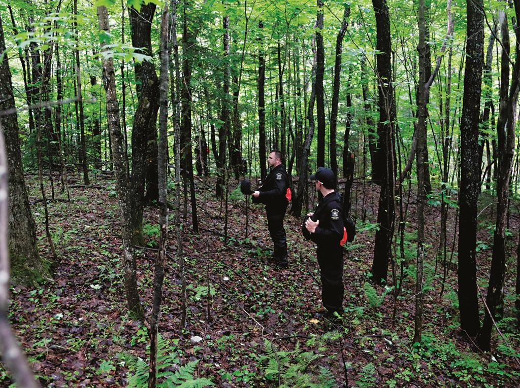 Corrections officers walk through woods Tuesday while searching for the escapees in Owls Head, N.Y. (AP Photo/Mike Groll)
