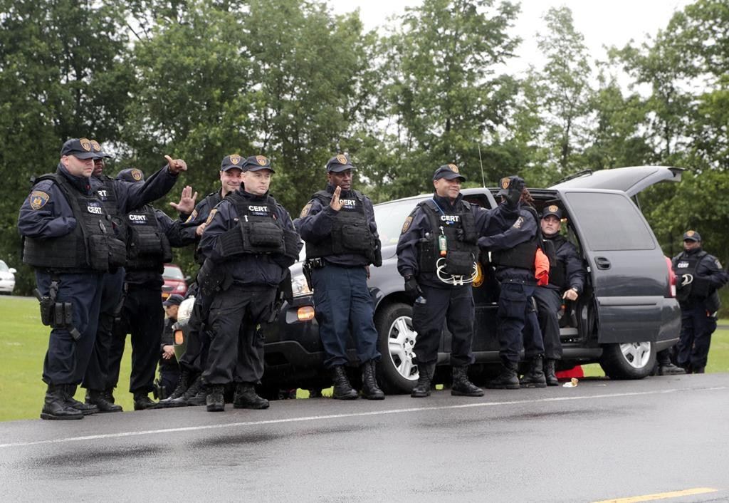Corrections officers wave to passing motorists who cheer them after the second of two escaped prisoners was apprehended on Sunday in Constable, N.Y. (AP Photo/Mike Groll)
