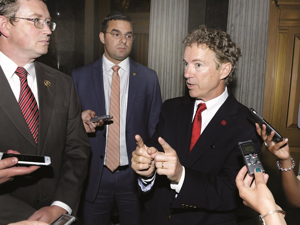 Sen. Rand Paul (R-KY) responds to reporters' questions as he leaves the Senate floor after making remarks on a rare working Sunday, on Capitol Hill, in Washington Sunday. (REUTERS/Mike Theiler)