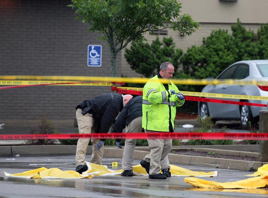 Boston police officers and detectives investigate the scene of a shooting Tuesday, in Roslindale, Mass. A man who had been under 24-hour surveillance by terrorism investigators was shot and killed after he lunged with a knife at a police officer and an FBI agent outside a pharmacy, authorities said.  (Mark Garfinkel/The Boston Herald via AP)