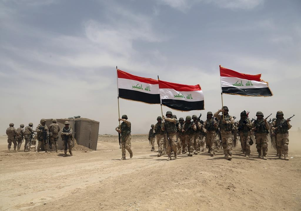 American soldiers, left, participate in a training mission with Iraqi soldiers outside Baghdad, Iraq. (AP Photo/Khalid Mohammed)