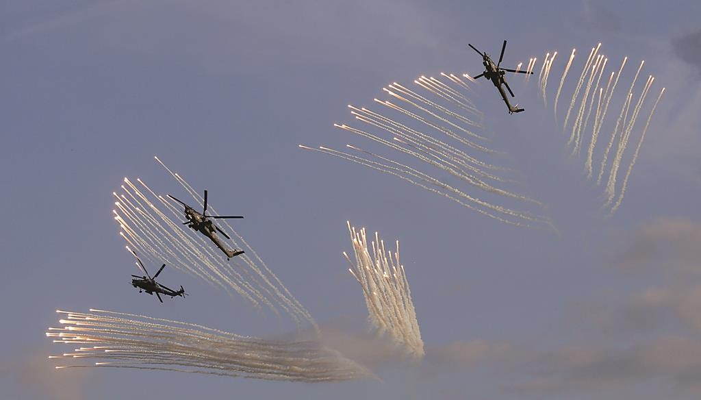 Russian military helicopters fly during the opening of the Army-2015 international military forum in Kubinka, outside Moscow, Russia, Tuesday. (REUTERS/Maxim Shemetov)