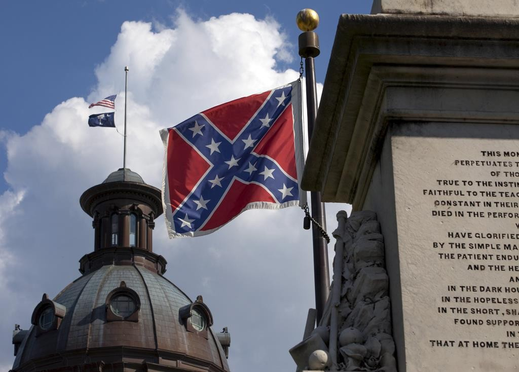 The United States flag and the South Carolina state flag fly at half staff above the South Carolina State House in Columbia, S.C., to honor the nine people slain on Wednesday. The Confederate flag, foreground, also flies on the grounds of the State House, at a separate Civil War memorial.  (REUTERS/Jason Miczek)