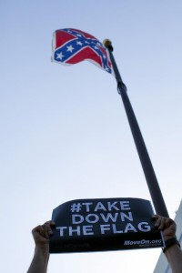 A protester holds a sign asking for the removal of the confederate battle flag that flies at the South Carolina State House in Columbia, SC. (REUTERS/Jason Miczek)