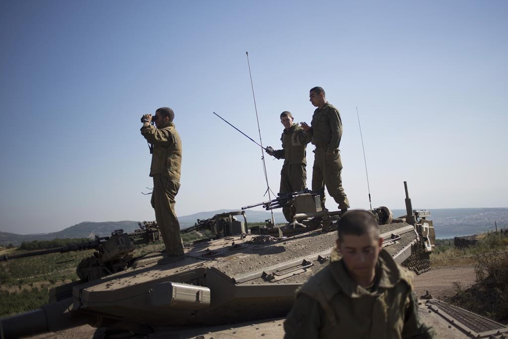 Israeli soldiers atop a tank watch smoke and explosions from the fighting between forces loyal to Syrian President Bashar Assad and rebels in the Druze village of Khader in Syria, as seen from the Golan Heights, Tuesday. (AP Photo/Ariel Schalit)