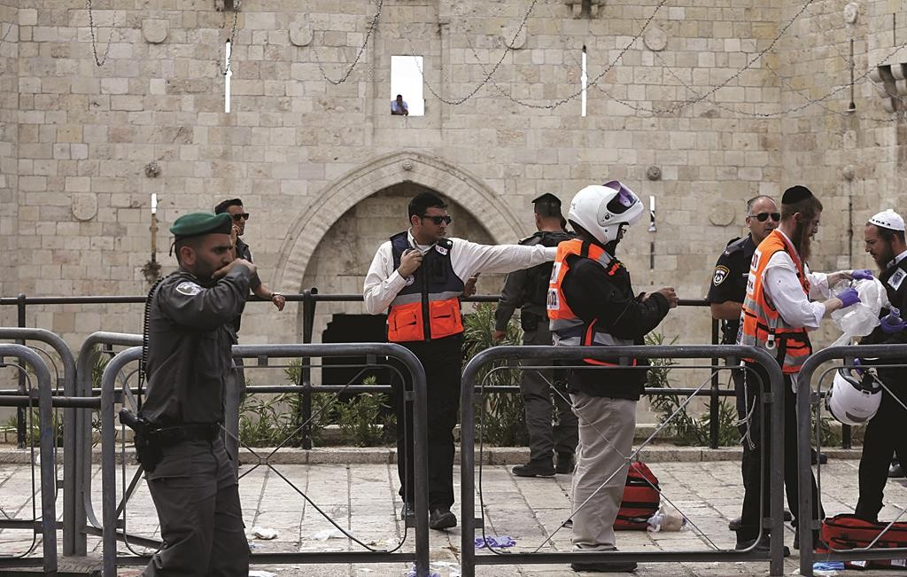 Israeli emergency personnel stand at the scene of a terror attack outside the Damascus Gate on Sunday. (REUTERS/Ammar Awad)