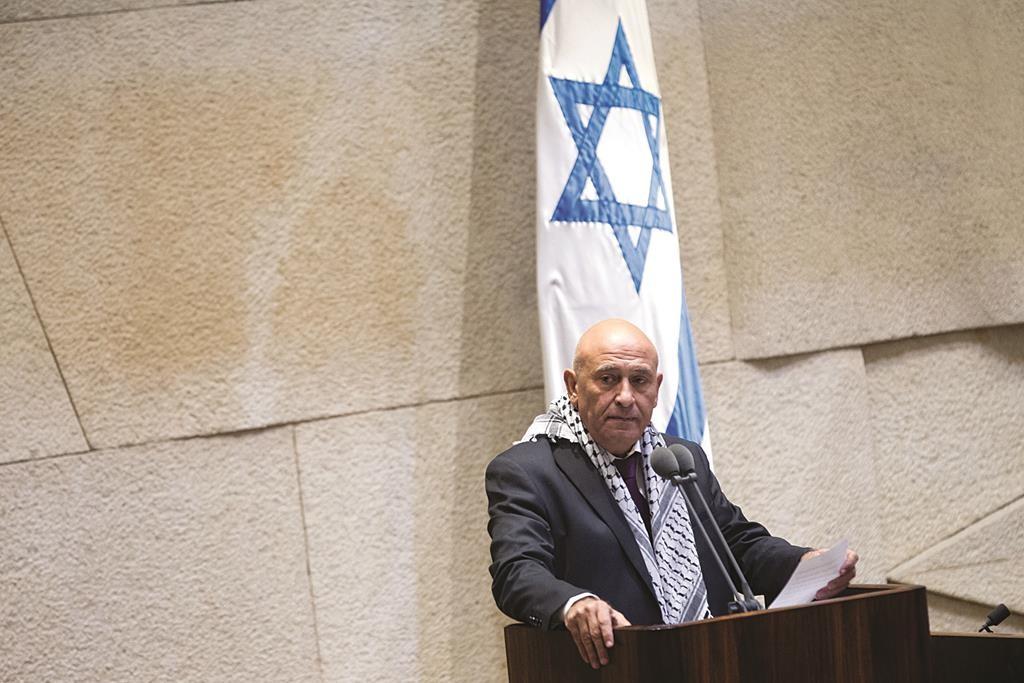 Arab Israeli parliament member Basel Ghattas wears a kafiya around his shoulders as he addresses the Knesset in 2014. (Miriam Alster/Flash90)