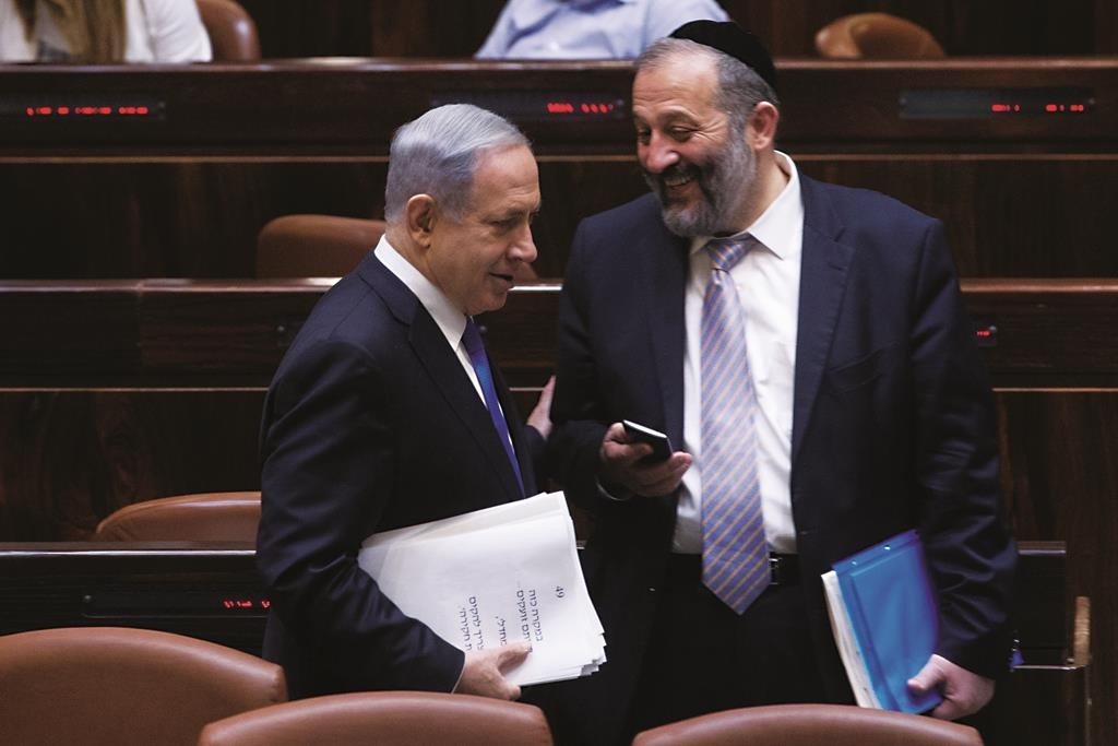 Israeli Prime Minister Binyamin Netanyahu seen with Economy Minister Aryeh Deri in the Knesset on Wednesday. (Miriam Alster/FLASH90)