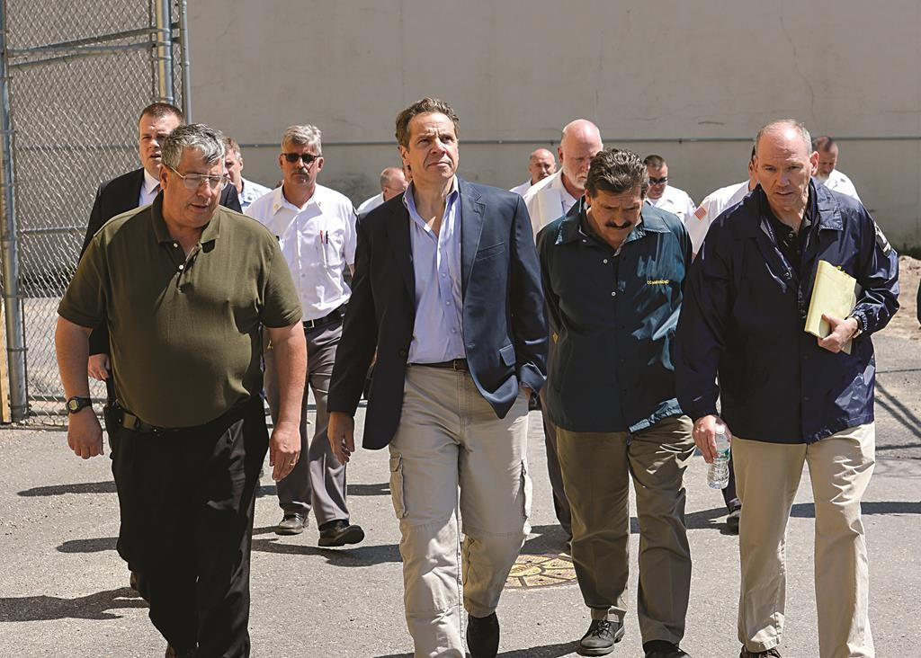 Gov. Andrew Cuomo, second from left in front, walking with Steven Racette, left, superintendent of Clinton Correctional Facility, in Dannemora, N.Y. Racette and his deputy in charge of security are among 12 more staff who have been put on administrative leave, officials said Tuesday. (Darren McGee/Officer of the New York Governor via AP)