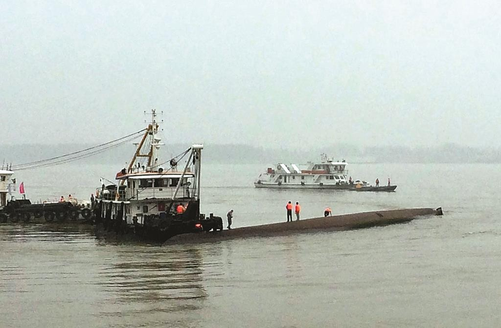Rescue workers stand on the capsized ship on the Yangtze River in central China's Hubei province Tuesday. (Chinatopix via AP)