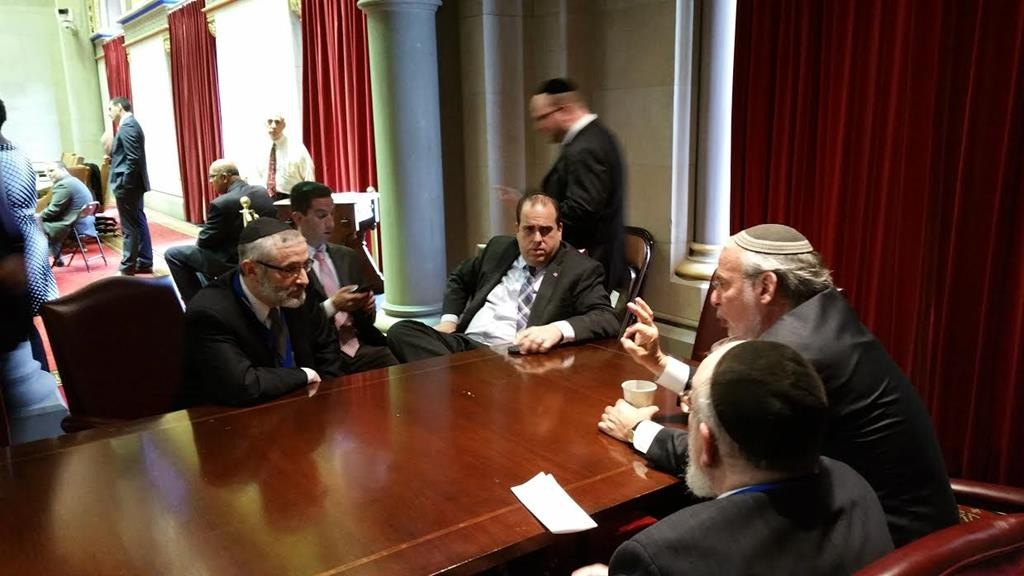 Rabbi Chaim Dovid Zwiebel (L) and Rabbi Shmuel Lefkowitz (center, facing away from camera), on Tuesday discuss the education tax credit and the East Ramapo school board with Assemblymen Dov Hikind (R), Michael Simanowitz (seated C) and Philip Goldfeder (seated, 2nd left) in Albany. (Hamodia Photo)