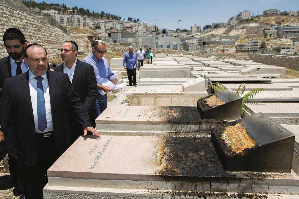 Minister for Religious Affairs David Azulay leading a delegation surveying desecrated graves at Har Hazeisim on Tuesday, where evidence of torching was seen. (Yonatan Sindel/Flash90)