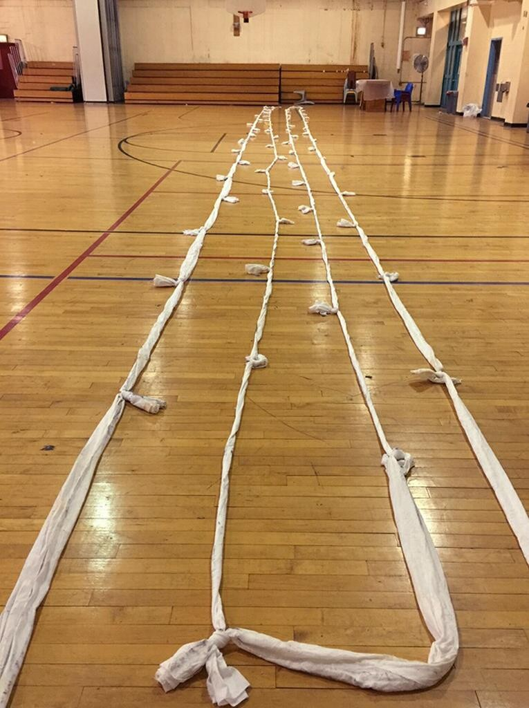 """Manhattan District Attorney's Office via AP A rope fashioned from 64 bed sheets tied together is shown stretched out on a gymnasium floor. (Bottom) A note from an inmate thanking Correction officer Patricia Howard for supporting """"the jail shopping network."""""""