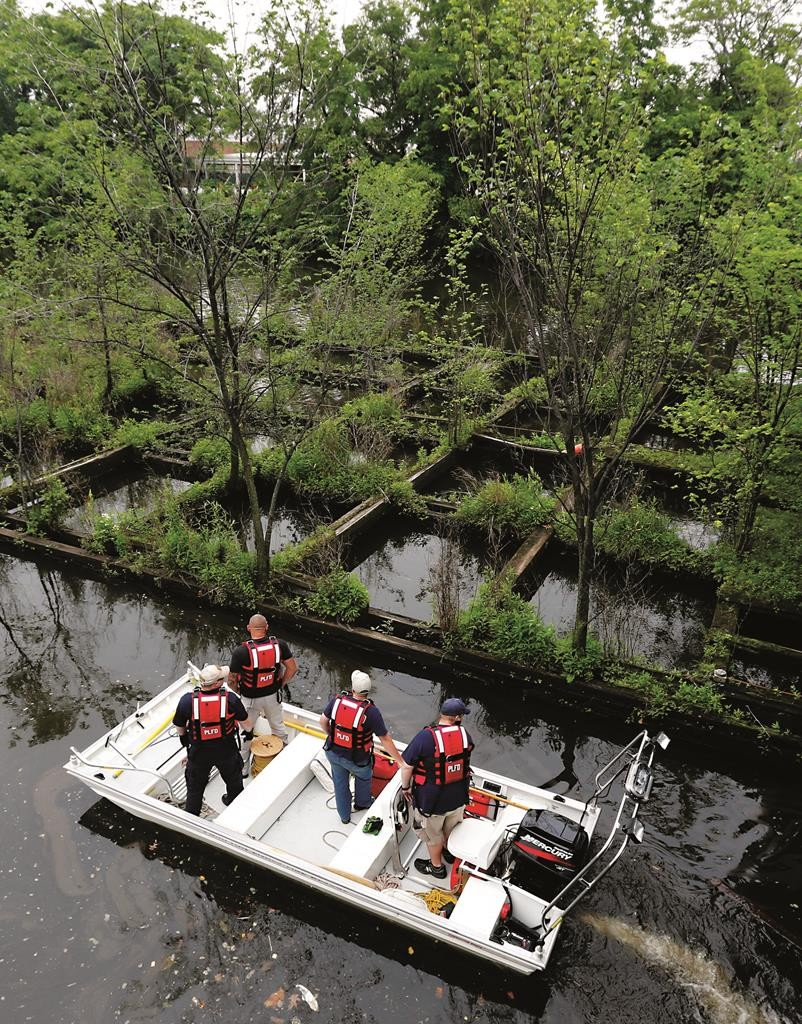Officials riding a rescue boat on Tuesday search the Passaic River for a man that was swept away during a flash flood a day earlier in Wallington, NJ. (AP Photo/Julio Cortez)