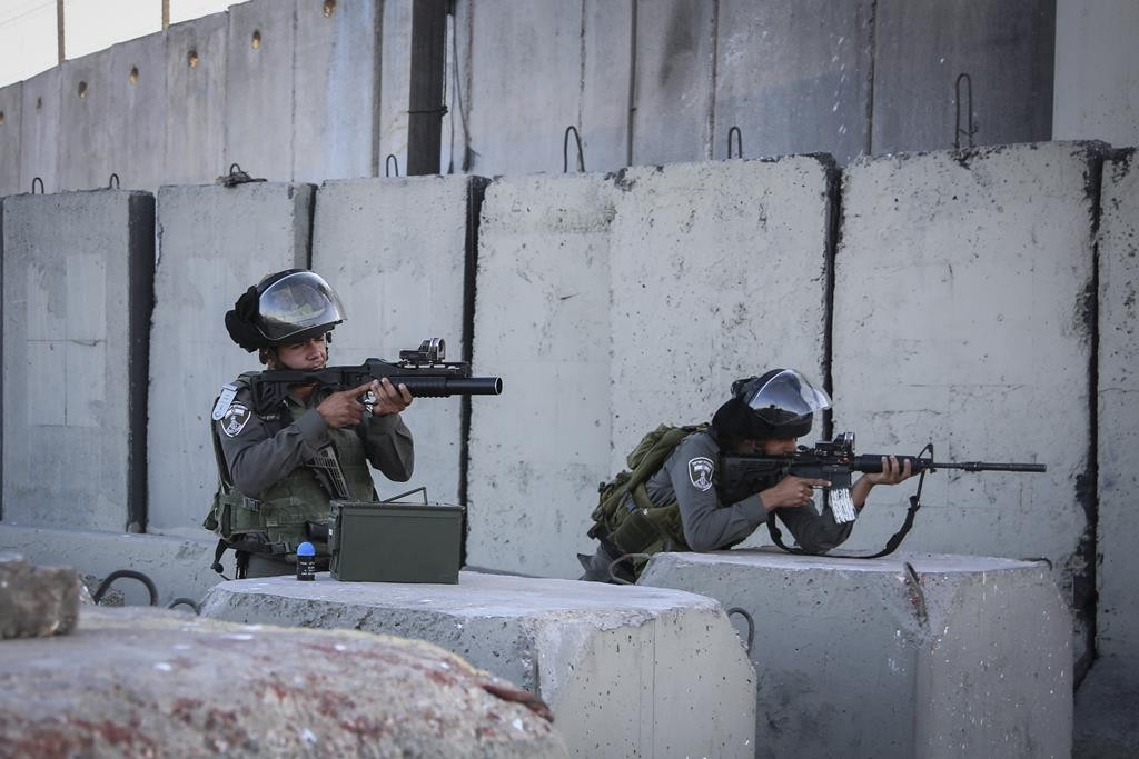 Israeli border police officers at the scene where guards opened fire on a man who tried to run the Qalandiya checkpoint Tuesday. (STR/Flash90)