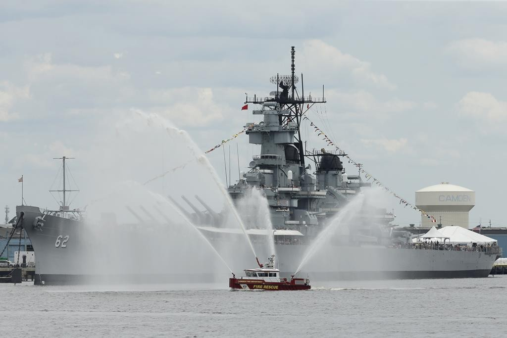 A fire rescue boat on Thursday sprays water near the USS New Jersey before a tall ships parade on the Camden waterfront. (AP Photo/Matt Slocum)