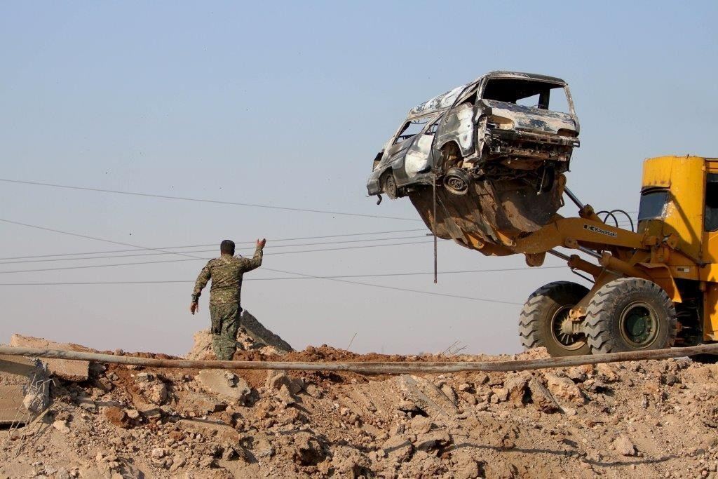 A Kurdish fighter guides a loader as it removes a damaged vehicle at the eastern entrance to the town of Tel Abyad, June 15, 2015. Kurdish-led militia, backed by U.S.-led coalition air strikes, gained control of the town, severing an Islamic State supply line. (REUTERS/Rodi Said)