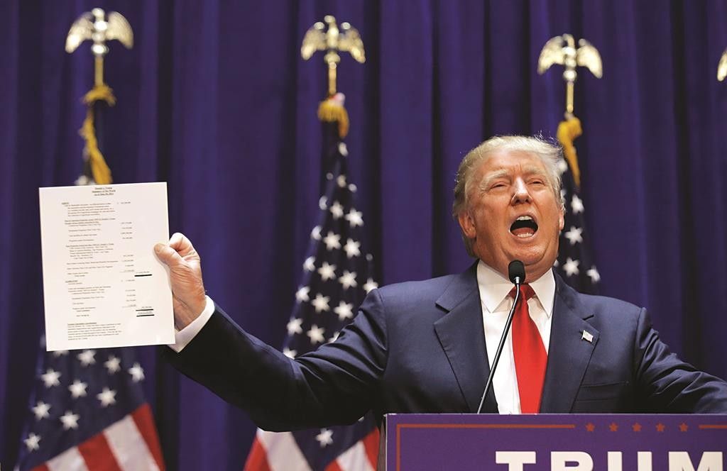 Republican presidential candidate Donald Trump holds up his financial statement showing his net worth as he formally announces his campaign for the 2016 Republican presidential nomination during an event at Trump Tower in New York Tuesday. (REUTERS/Brendan McDermid)