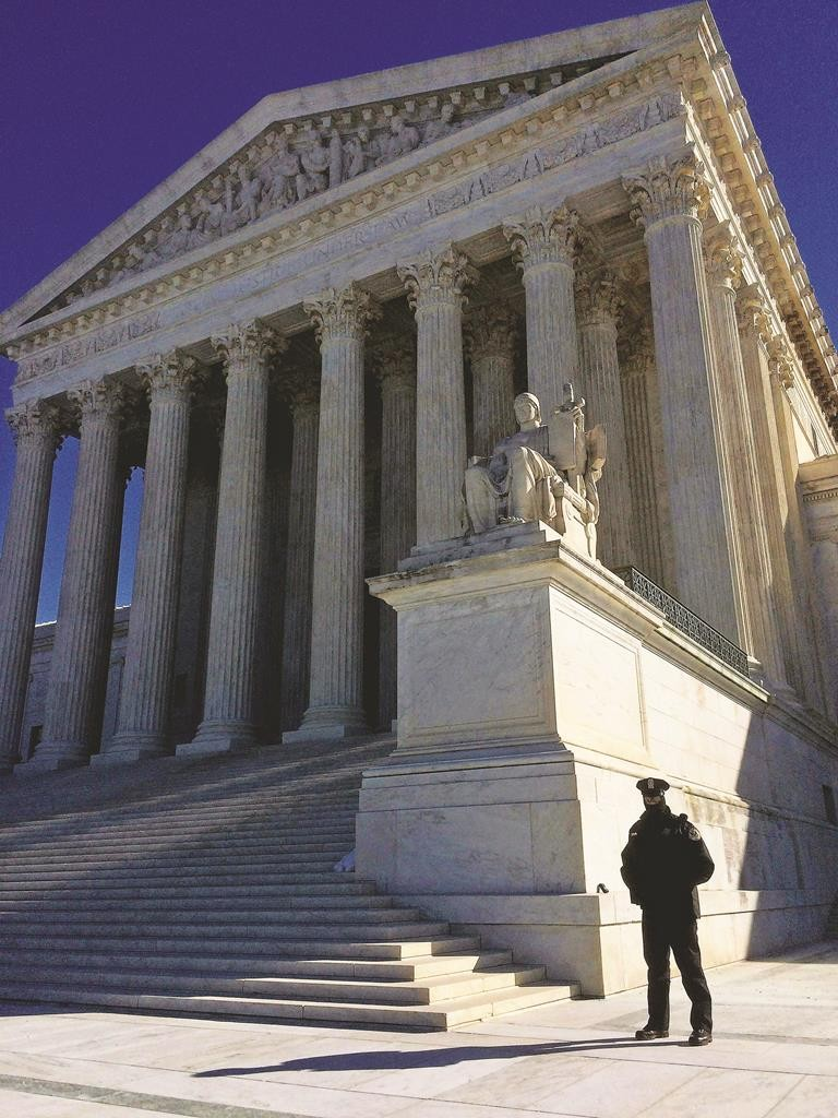 WASHINGTON, DC - FEBRUARY 24: (EDITORS NOTE: Image was created using an iPhone.) A guard stands outside the United States Supreme Court prior to oral arguments starting in the case Henderson v United States February 24, 2015 in Washington, DC. The Supreme Court heard arguments in the case of Tony Henderson, a former U.S. Border Patrol agent who was convicted of drug offences and subsequently sought to either transfer or sell his 19 guns to his wife. He is challenging lower court orders to block the sale or transfer. (Photo by Chip Somodevilla/Getty Images)