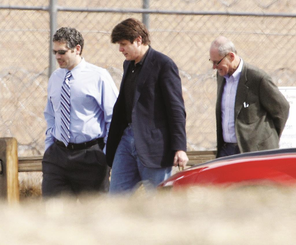 In this March 15, 2012 photo, former Illinois Gov. Rod Blagojevich (C) walks with attorneys as he arrives at the Federal Correctional Institution Englewood in Littleton, Colo., to begin serving his 14-year sentence for corruption.  (AP Photo/Ed Andrieski, File)