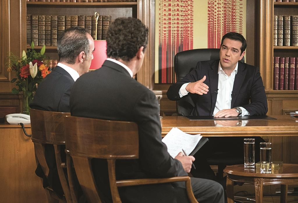 Greece's Prime Minister Alexis Tsirpas, R, speaks to journalists during an interview from his office at Maximos Mansion in Athens.  (Andrea Bonetti/Greek Prime Minister's Office via AP)
