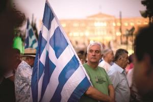 Demonstrators gather near the Greek Parliament during a rally against the government's agreement with its creditors in Athens, in central Athens, Tuesday. (AP Photo/Emilio Morenatti)