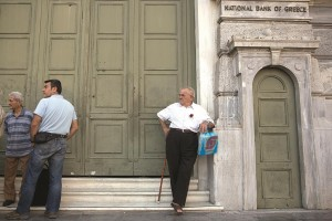 Pensioners stand outside the main gate of the National Bank of Greece as they wait to withdraw a maximum of 120 euros ($134) for the week in Athens, on Tuesday. (AP Photo/Petros Giannakouris)