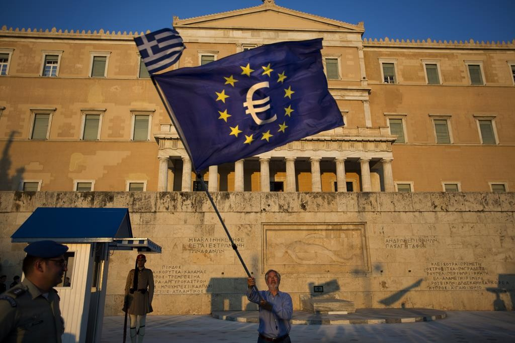 A demonstrator waves a European Union flag in front of the Greek Parliament during a rally in Athens, Thursday.  (AP Photo/Emilio Morenatti)