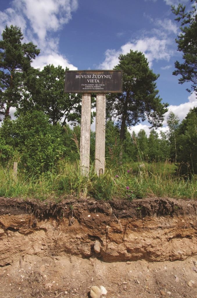 A sign marking a mass grave, with signs of construction in the foreground.