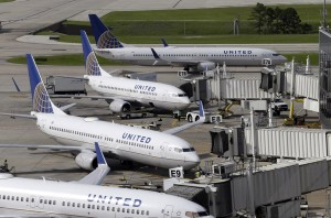"""United Airlines planes are parked at their gates as another plane, top, taxis past them at George Bush Intercontinental Airport Wednesday, in Houston. All United Continental flights in the U.S. were grounded temporarily Wednesday due to computer problems. Less than two hours later, United requested the Federal Aviation Administration lift the ground stop order. United cited """"network connectivity"""" for the problems.  (AP Photo/David J. Phillip)"""