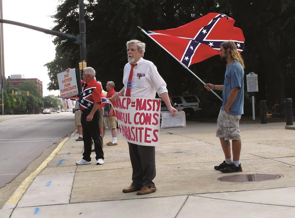William Cheek, left, Nelson Waller, center, and Jim Collins, right, protest proposals to remove the Confederate flag from the grounds of the South Carolina Statehouse on Monday, in Columbia, S.C.  (AP Photo/Jeffrey Collins)