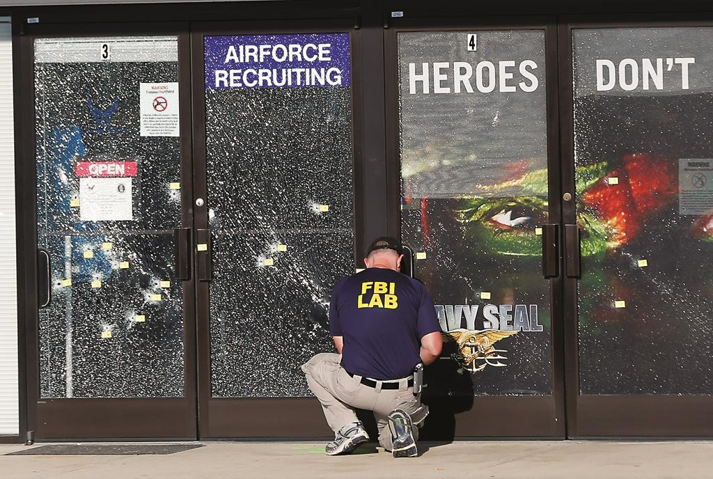 An FBI investigator investigates the scene of a shooting outside a military recruiting center in Chattanooga, Tenn.  (AP Photo/John Bazemore)