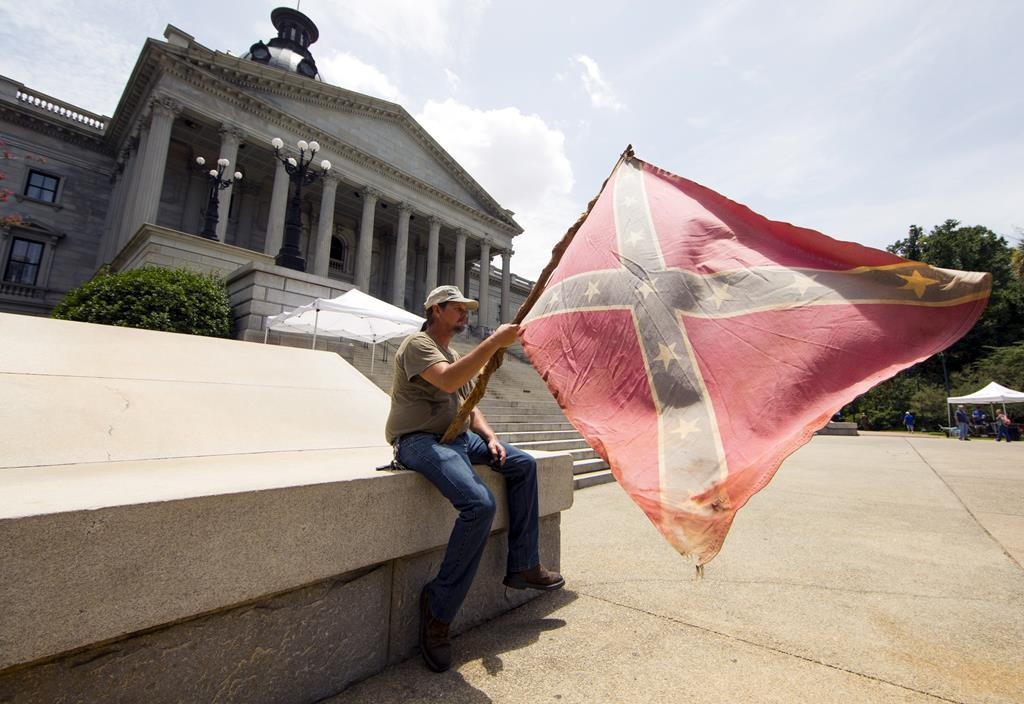 A man holds a confederate flag outside the statehouse in Columbia, South Carolina, Thursday hours before Gov. Nikki Haley signed a bill to remove the flag from statehouse grounds.  (REUTERS/Jason Miczek)