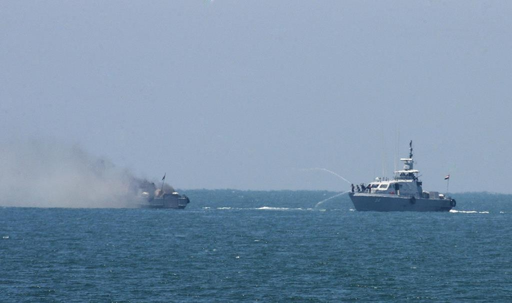 Egyptian navy vessel hoses down another that is on fire in the Mediterranean Sea Thursday. (AP Photo/Eyad Baba)