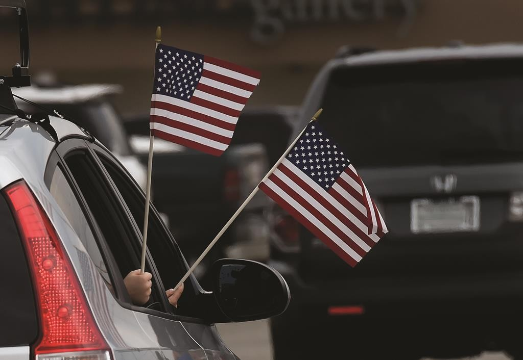 Two boys wave American flags out a car window as they arrive at a makeshift memorial in front of the Armed Forces Career Center. (AP Photo/Mark Zaleski)