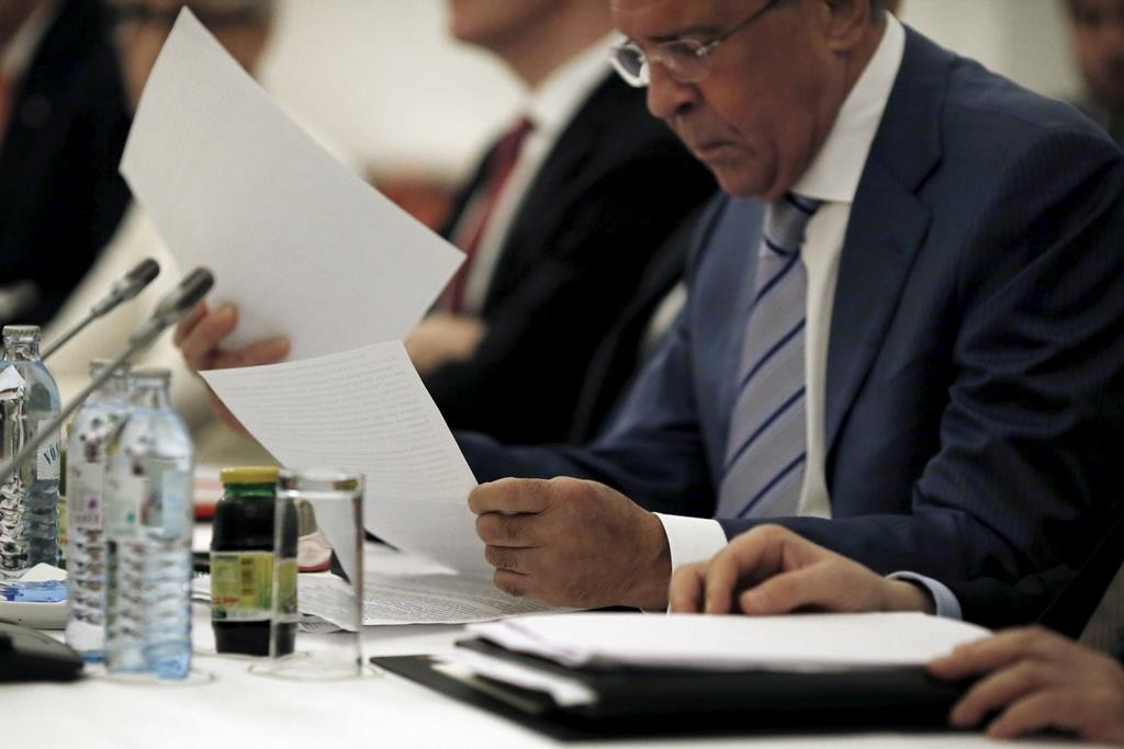 Russian Foreign Minister Sergei Lavrov reads documents during a meeting with foreign ministers and delegations from Germany, France, China, Britain, the U.S. and the EU at a hotel in Vienna, Austria Monday.  (REUTERS/Carlos Barria)