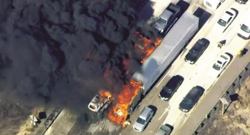 In this frame from video provided by NBC4, smoke rises from vehicles as a fast-moving wildfire swept across a freeway Friday, near Hesperia, California.  (NBC4 via AP)