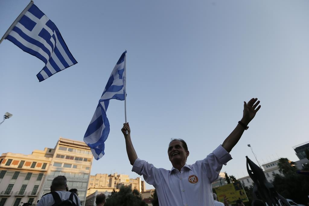 A supporter of the 'No' vote waves a Greek flag after the referendum's exit polls at Klafthmonos square in Athens, on Sunday. (AP Photo/Petr David Josek)