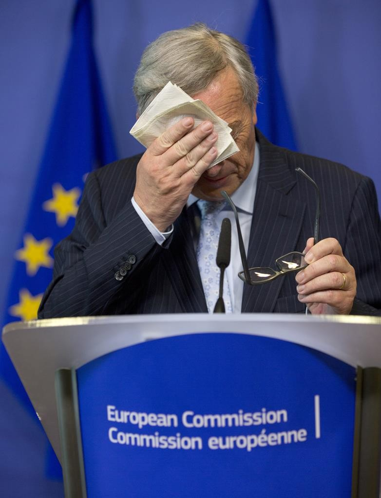 European Commission President Jean-Claude Juncker wipes his face before speaking during a media conference at EU headquarters in Brussels on Wednesday.   (AP Photo/Virginia Mayo)