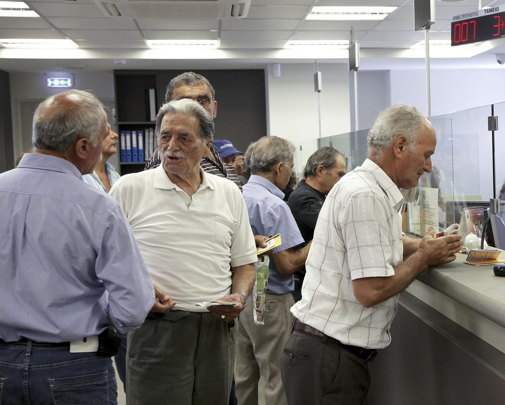 People make transactions at a counter inside a Piraeus Bank branch in the city of Iraklio on the island of Crete, Greece, Monday. (REUTERS/Stefanos Rapanis)