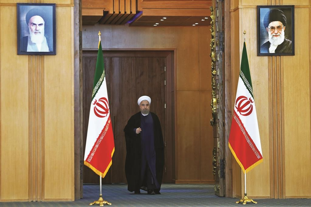 Iran's president Hassan Rouhani arrives for an address to the nation after a nuclear agreement was announced in Vienna, in Tehran, Iran, Tuesday, July 14, 2015. After long, fractious negotiations, world powers and Iran struck a historic deal Tuesday to curb Iran's nuclear program in exchange for billions of dollars in relief from international sanctions - an agreement aimed at averting the threat of a nuclear-armed Iran and another U.S. military intervention in the Middle East. Pictures of the late Iranian revolutionary founder Ayatollah Khomeini, top left, and supreme leader Ayatollah Ali Khamenei hang on the wall. (AP Photo/Ebrahim Noroozi)