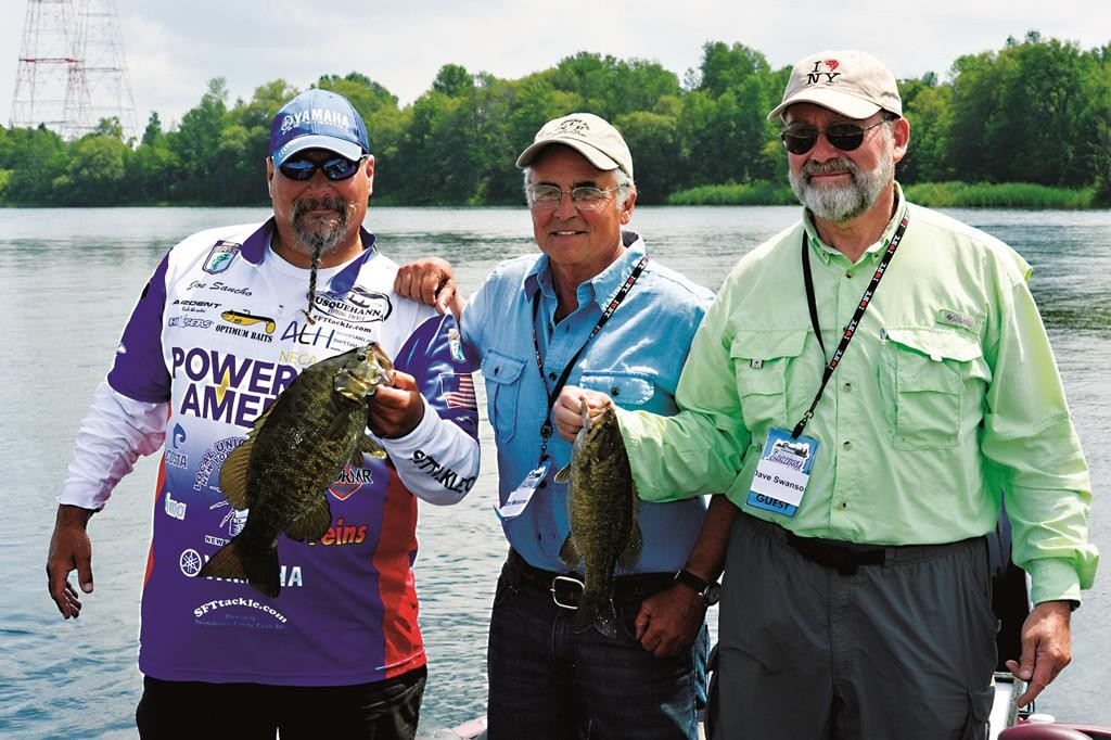 Three fishermen hold up their catches on Sunday during Gov. Andrew Cuomo's Bassmaster Challenge in Massena, N.Y. (Office of Gov. Cuomo)