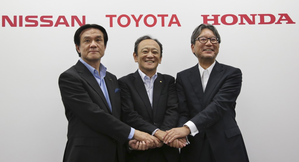 "Toyota Motor Corp. executive Kiyotaka Ise, center, Nissan Motor Co. executive Hitoshi Kawaguchi, left, and Honda Motor Co., executive Toshihiro Mibe join hands during a press conference on the collaboration of hydrogen fueling stations in Tokyo, on Wednesday, July 1. Toyota, Nissan and Honda are working together to get more fuel-cell vehicles on roads in what they call Japan's big push toward ""a hydrogen society."" (AP Photo/Koji Sasahara)"