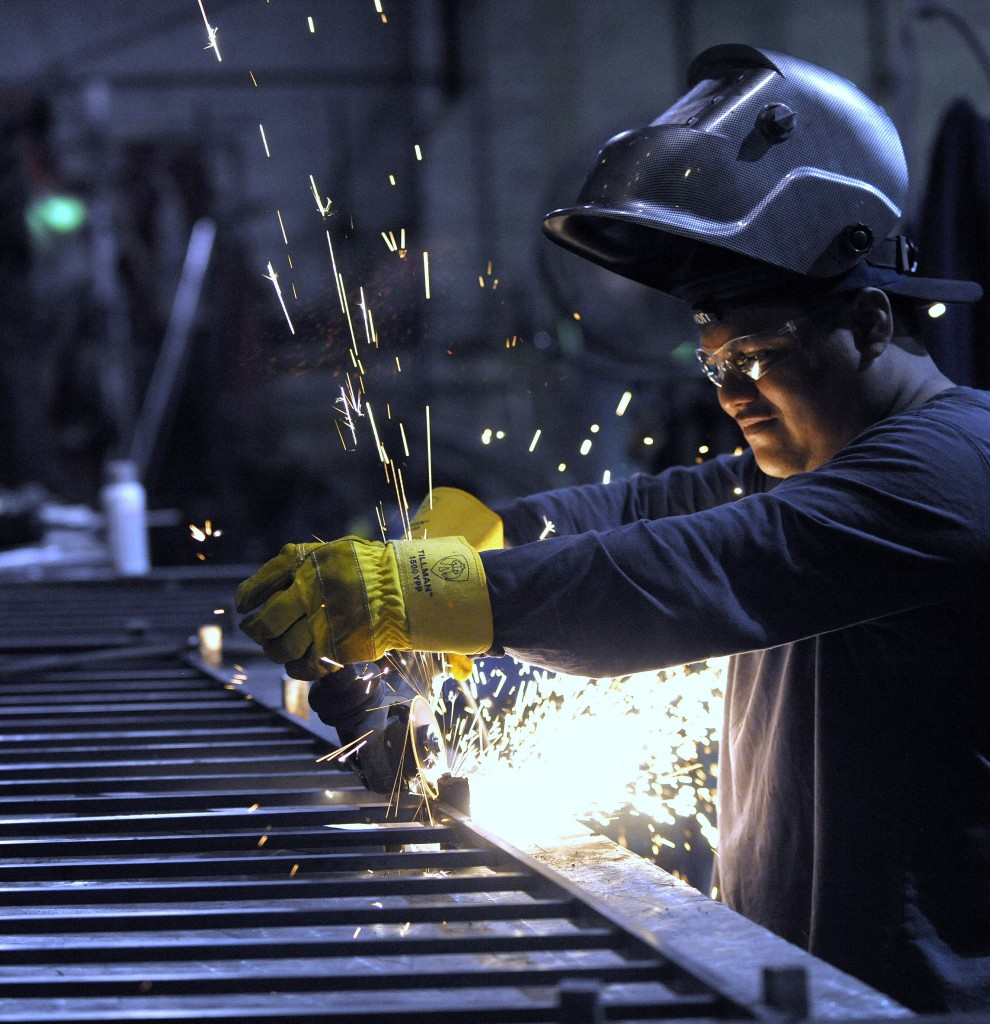 In this photo, taken on June 11, machinist Angel Altamirano, 32, of River Rouge, Michigan, grinds a guardrail for a staircase in Detroit. On Wednesday, July 1, the Institute for Supply Management, a trade group of purchasing managers, said its manufacturing index rose in June. (Todd McInturf /The Detroit News via AP)