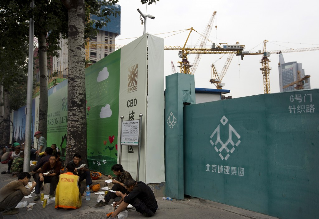 Workers eat lunch outside a construction site at the Central Business District of Beijing Wednesday. (AP Photo/Andy Wong)